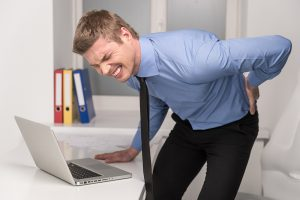 handsome man feeling pain in back. Businessman suffering from back pain at office